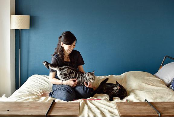 ベッドで猫たちと戯れる女性