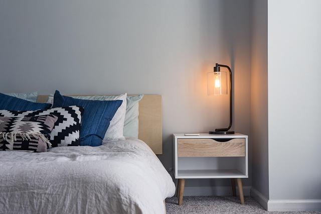 寝室のベッドとサイドテーブルのランプ